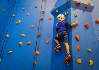 little boy climbing wall in sport center