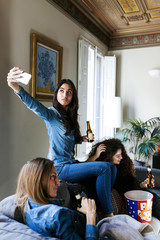 Young woman with beer bottle taking a selfie while seating on the couch with her friends