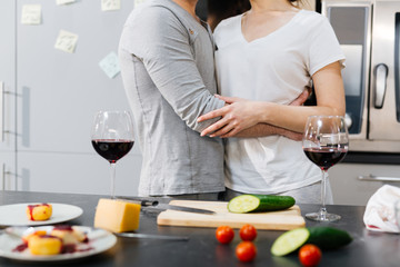 Bonding couple in embrace standing by kitchen table