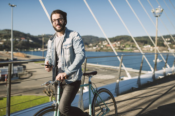 Smiling young man with fixie bike on a bridge