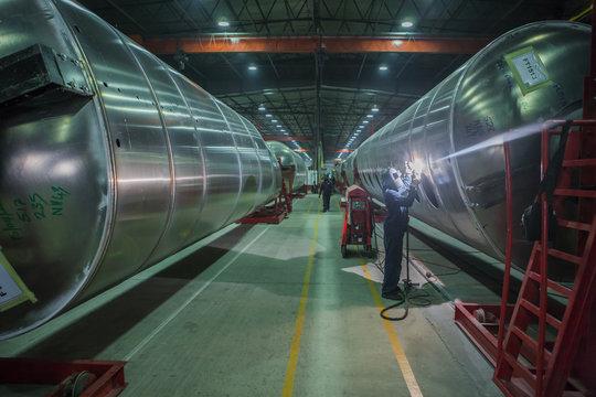 Man welding large steel tank in factory