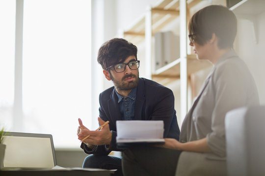 Modern middle eastern man wearing creative haircut and glasses listening intently to his colleague during  discussion of business ideas in modern office