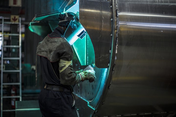 Man welding steel tank in factory