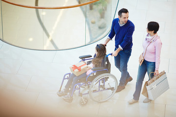 Husband and wife talking during shopping with their disabled daughter