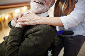 Smiling aged man in wheelchair and his caregiver