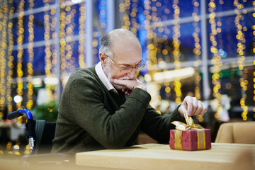 Disabled senior man looking at gift-box on table