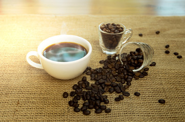 Cup of black coffee and coffee beans on sackcloth
