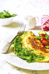 Omelet with cheese and arugula - healthy diet breakfast on white