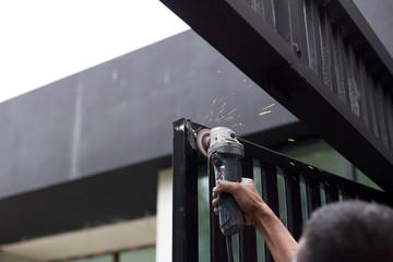 Hand holding steel cutting grinder working on metal door