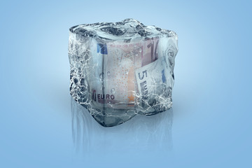 Frozen Euro EUR money in ice cube on a blue background