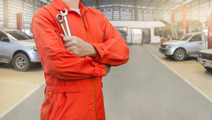 Mechanic holding wrench in car garage, Mechanic and tools concept.