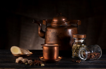 masala chai in vintage copper teapot and cups, spices and spicy