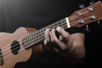 Man playing ukulele finger stlye with chord on black background