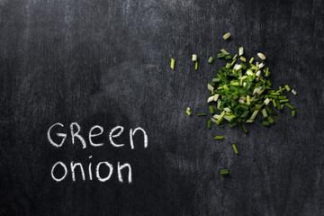 Green onion over dark chalkboard background