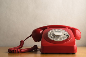 Retro Red Telephone on Light Wood Veneer Table