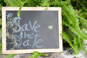 """Save the date"" word written on blackboard, wedding concept"