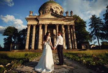 couple holding hands near antique columns