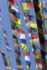coloured prayer flags against a blue sky