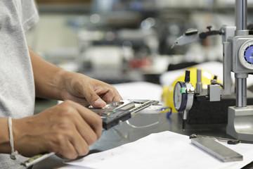 Technician measure part by vernier caliper