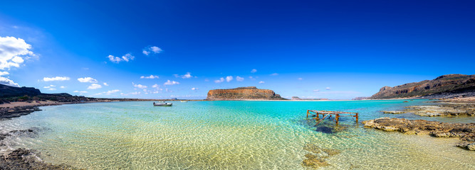 Amazing panorama of Balos Lagoon with magical turquoise waters, lagoons, pier, boat, tropical beaches of pure white sand and Gramvousa island on Crete, Greece
