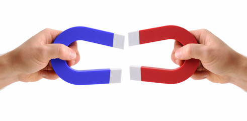 hands holding magnets one red and one blue