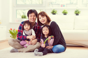 Young happy family with pretty daughters playing and having fun