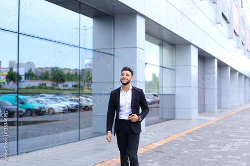 1ff9dd44565 Arabic guy in business center stands smiling walking slow