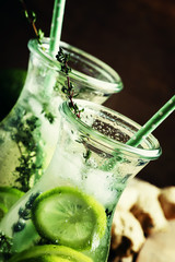 Ginger ale with lime, thyme and ice, vintage wooden background,