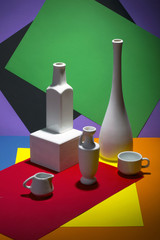 Натюрморт с вазами и чашками на цветном фоне