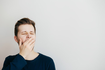 Young yawing man clodse his mouth  with his hands on a light background