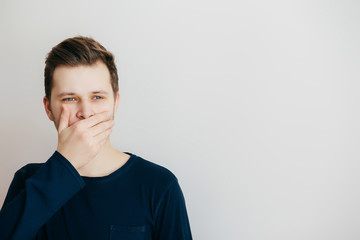 Young man closed a mouth hands on a light background