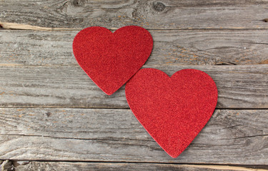 2 red hearts on a rustic wood background