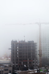 A new residential building under construction in the morning mist. Iron-concrete frame building. Builders in the formwork assembly.