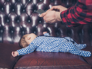 Man taking photo of sleeping baby