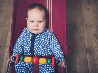 Confused baby in vintage bouncy chair