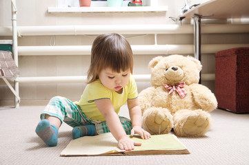 little girl reading book indoor in her room on carpet with toy Teddy bear, cute child playing school, children education and development, happy childhood