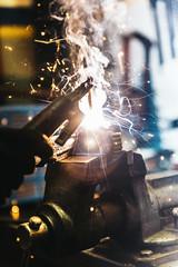 Mechanic man welding metal material in garage.