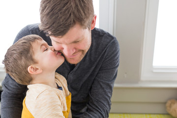 Young boy kissing father on cheek
