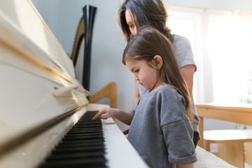 Girl and woman playing piano