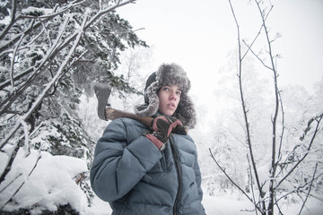 boy in the winter forest. The boy with an ax in his hand. boy in winter clothes. Snow in the woods. a lot of snow. young lumberjack.