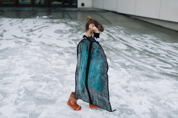 Young girl walking in snow, carrying dress in clothes protector