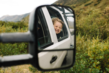 Vehicle wing mirror, reflecting young boy looking out of car window