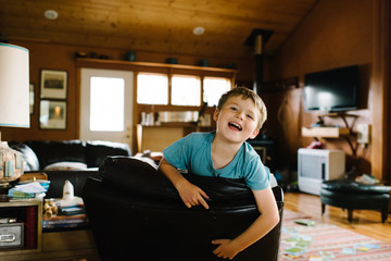 Portrait of young boy clambering over chair