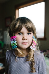 Portrait of young girl with colourful hair clips in hair