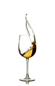splash of white wine in the glass on a white background