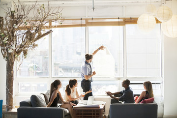 Businessman showing blueprint to colleagues during meeting in office