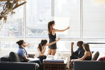 Businesswoman showing blueprint to colleagues in creative office