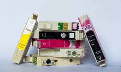 Empty ink cartridges with labels of various colors stacked on wh