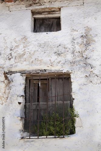 Viejas ventanas con postigos de madera y rejas oxidadas una pared ...