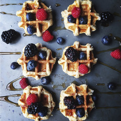 Overhead view of berry fruits and honey garnished on waffle